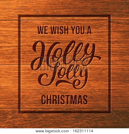 We wish you a Holly Jolly Christmas typographic text on wooden background. Vintage vector greeting card design with hand letteting for Xmas and winter holidays.