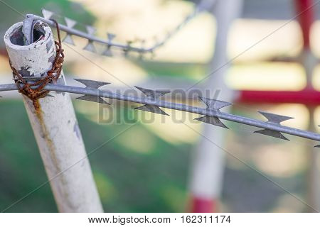Close-up detail of razor ribbons a type of barbed wire tied to metal poles at a military checkpoint. Border control and illegal immigration concept.