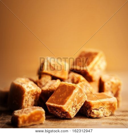 Salted caramel pieces and sea salt macro on wooden board with copy space warm toned