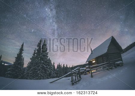 Fantastic night landscape glowing by milky way. Dramatic wintry scene with snowy house. Carpathians, Ukraine, Europe. Toned like Instagram filter