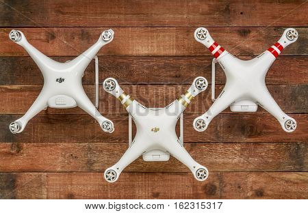 FORT COLLINS, CO, USA - DECEMBER 18, 2016:  Three generations of DJI quadcopter drones  - Phantom 4 (from left), 3 and 2, top view of aircraft against rustic wood.