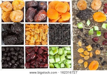 Assorted dried fruits (raisins, apricots, figs, prunes, goji, cranberries, blueberries, prunes) in boxes on a wooden background