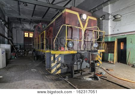 Old soviet shunting diesel locomotive in the abandoned room for servicing