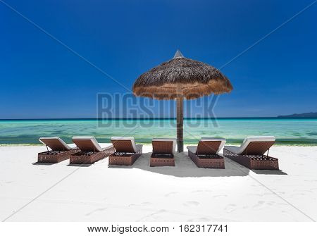 Sun Umbrella And Beach Beds On  Seashore