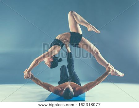 Young couple practicing acro yoga on mat in studio together