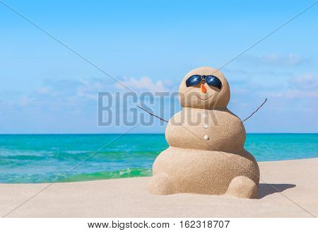 Positive sandy snowman in black eyeglasses and carrot nose at ocean beach. Happy New Year and Merry Christmas travel destinations for tropical vacations concept