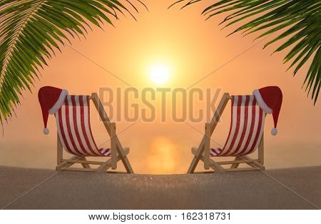 Two striped deckchairs with red Santa hats for romantic couple at ocean sandy beach under palm leaves during sunset. Happy New Year and Merry Christmas travel destinations to hot countries concept