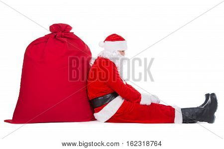 Tired Santa Claus have rest sitting near big Christmas sack full of presents gifts and surprises isolated on white background New Year or xmas holiday concept