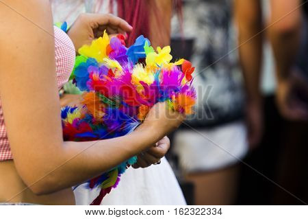 Close up on arms of unidentifiable woman holding colorful bouquet of feathers in a crowd