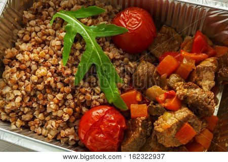 Healthy food in foil box closeup. Russian kasha buckwheat porridge with dried tomatoes and beef stew. Restaurant dishes delivery, lunch for diet