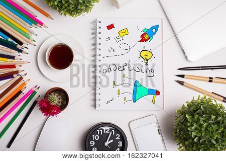 Top view of modern office workplace with colorful supplies coffee cup plants and notepad with creative sketch. Advertising concepty