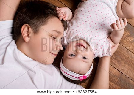 Brother hugging his newborn sister. View from above.