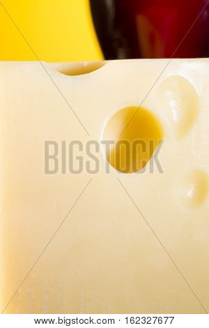 The big piece of cheese on a background of a glass of wine. On a yellow background
