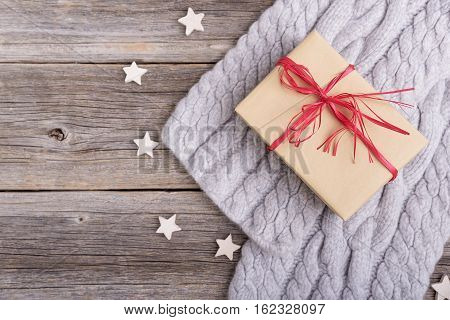 Winter scarf and gift box on the background of the old wooden boards.