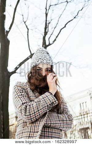 young pretty stylish modern hipster girl outside on winter street, fashion coat, hairstyle, make up, lifestyle people concept close up citylife