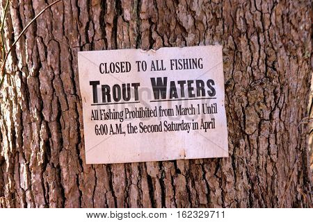 Sign stapled to a tree along a stream warning fisherman that opening day of trout season is not until 2nd Saturday in April.