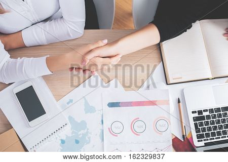 Top view of two white women shaking hands at office desk with financial reports and other items. Partnership concept