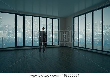 Thoughtful businessman in modern unfurnished interior with wooden floor concrete walls and panoramic windows with city view and daylight. 3D Rendering