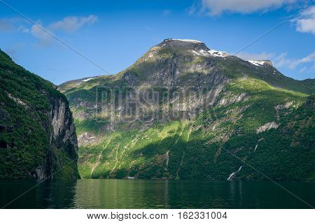Geiranger fjord landscape at morning sun beams, Scenic fjord landscapes of Norway fairytale.