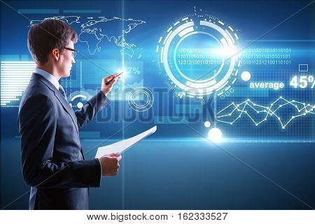 Man with document in hand managing abstract business panel on digital background. Finance concept