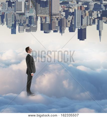 Thoughtful businessman on creative upside down city and cloudy sky background