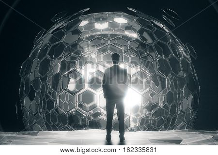 Back view of businessman standing in front of cellular silver sphere on dark background. 3D Rendering. Technology concept