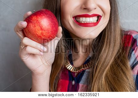 Close up view on the woman with healthy toothy smile and red apple
