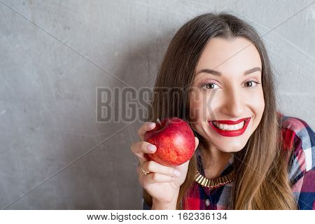 Young woman with toothy smile and red apple on the gray wall background
