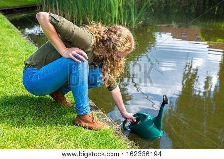 Young caucasian woman filling green caster with water in pond