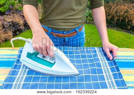 Young woman ironing tea towel with iron outdoors