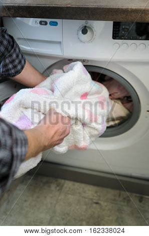 Hand man takes things washed with the washing machine.