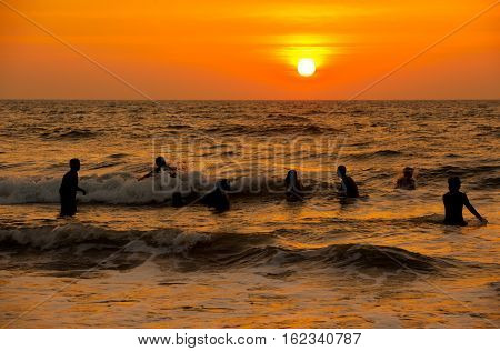 People sunset on the sea in India.