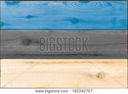 Timber planks of wood that have been painted or stained in the colors of an Estonian flag as a background