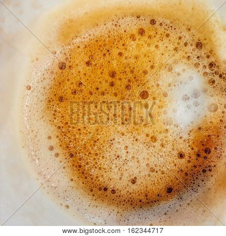 An extreme close up of coffee froth with milk in the paper cup.