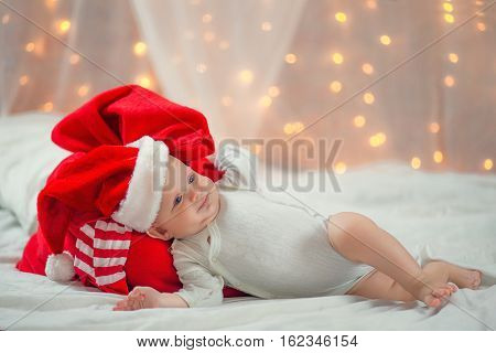 Beautiful little baby liyng with Santa Claus red bag on bed. New Year's holidays.