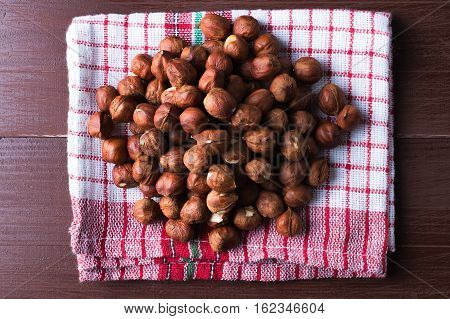 Hazelnuts on a vintage kitchen dishcloth. Brown wooden table. Flat lay top view. Vegan healthy food concept.