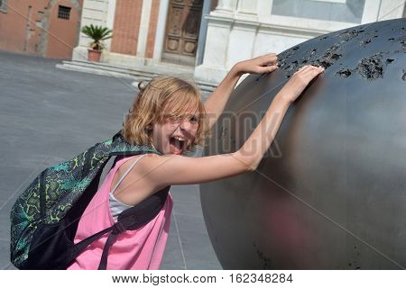 Girl with back bag reaches funnily loud in a piece of art on the Piazza dei Cavalieri in the city of Pisa, Italy