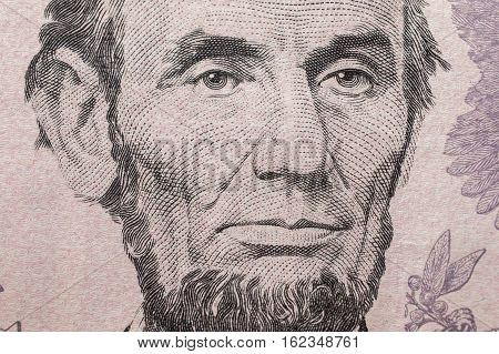 Portrait of US President Abraham Lincoln on the five dollar bill background of the money five dollar bills front side obverse. background of dollars close up