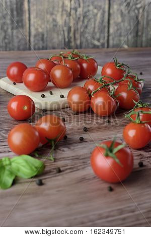 Scattered cherry tomatoes with pepper and leaves of basil on the wooden, brown table with the light wooden board.