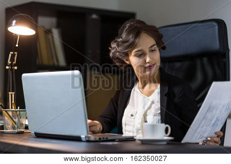 Portrait of a  businesswoman sitting at her workplace in office and work with documents