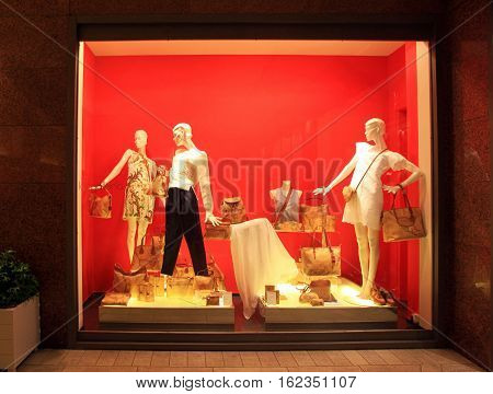 MONTECATINI, ITALY -  JANUARY 8, 2016: fashion boutique display window with female mannequins in fashionable dresses with bags in the night