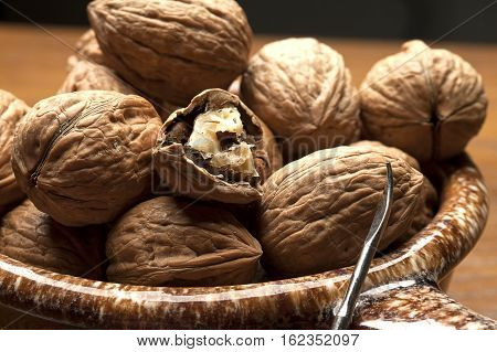 Mostly unshelled walnuts in bowl with a pick.