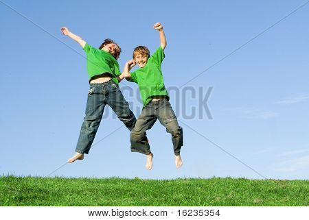 happy children jumping on hill