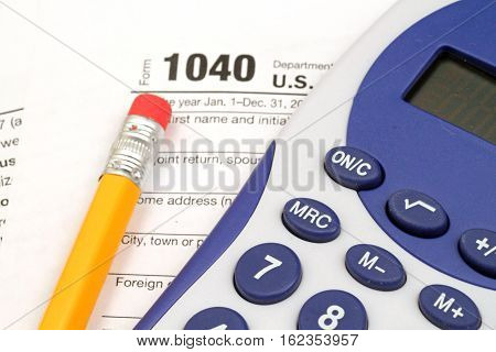 A close up on IRS form 1040 with tax prep tools
