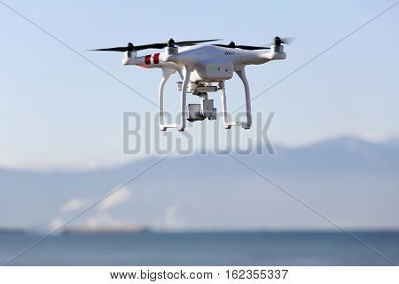 KAGAWA, JAPAN - DECEMBER 15, 2016: White remote controlled Drone Dji Phantom 3 equipped with high resolution video camera hovering in air with shore and clear blue sky