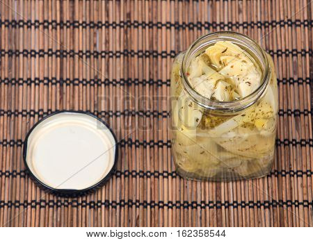 Food of love, marinated artichokes in jar on bamboo placemat