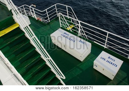 Two white boxes with life jackets on deck of cruise ship