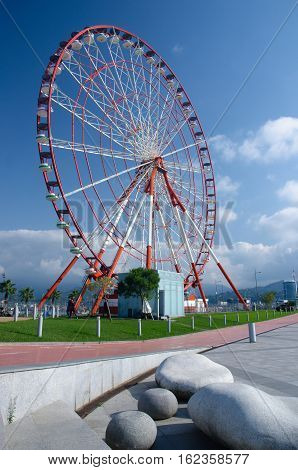 Ferris wheel on the Batumi seaside on sunny day with beautiful stone-shaped benches,Georgia, Adzharia