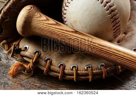 A close up image of an old used baseball, baseball glove, and wooden bat.
