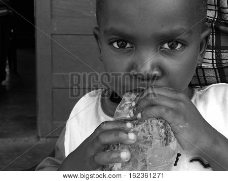 Young Child from Ghana, West Africa drinking water